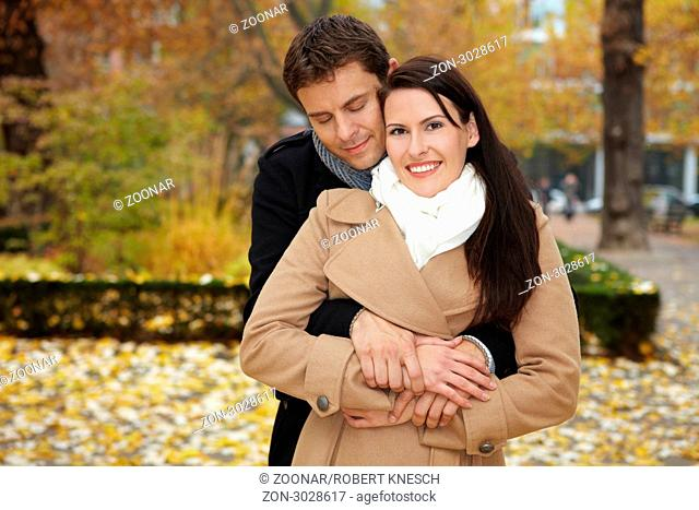 Mann kuschelt sich an Frau im herbstlichen Park