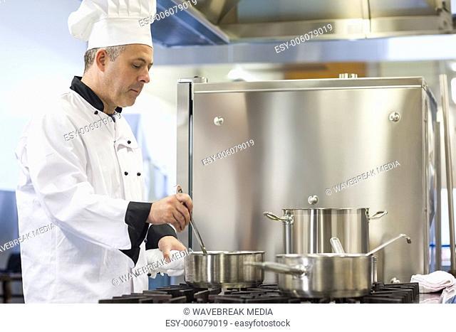 Focused head chef stirring in pot