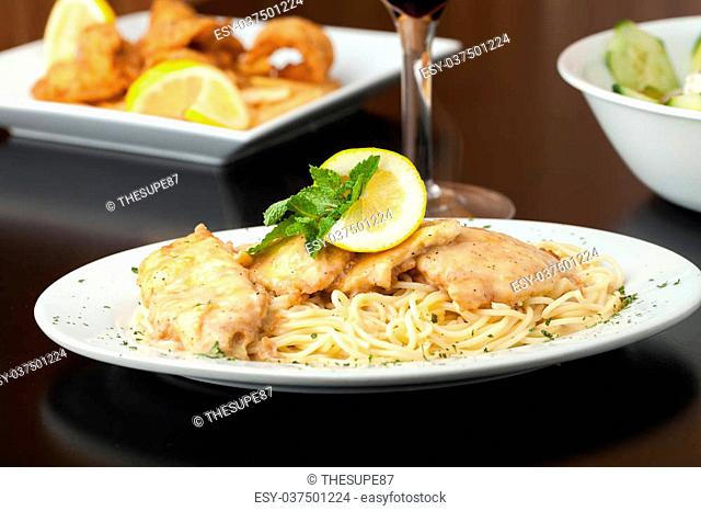 Chicken francaise or francese plated with pasta with salad and fried shrimp appetizer in the background