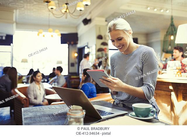 Smiling creative businesswoman using digital tablet and laptop in cafe