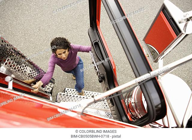 Young woman climbing into a truck