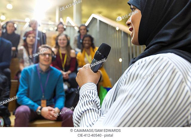 Smiling businesswoman in hijab speaking to audience with microphone