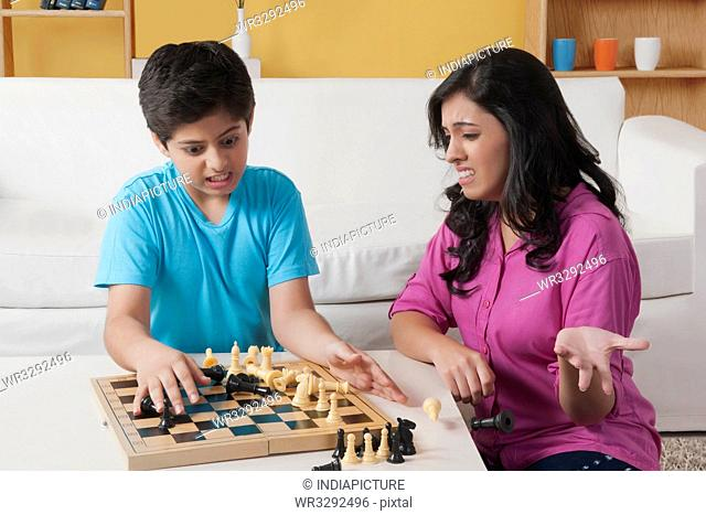 Sister and brother playing chess in living room