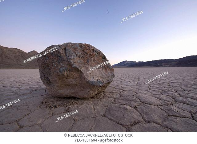 A solitary rock sitting on a dry lake bed in Death Valley