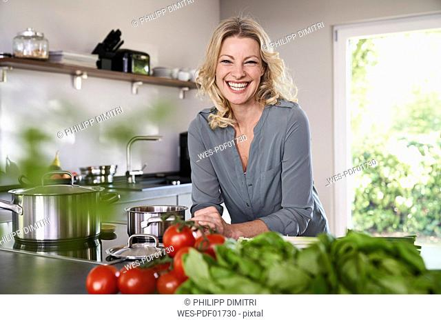 Portrait of happy woman cooking in kitchen