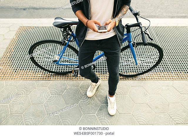 Teenager with a bike in the city, using smartphone