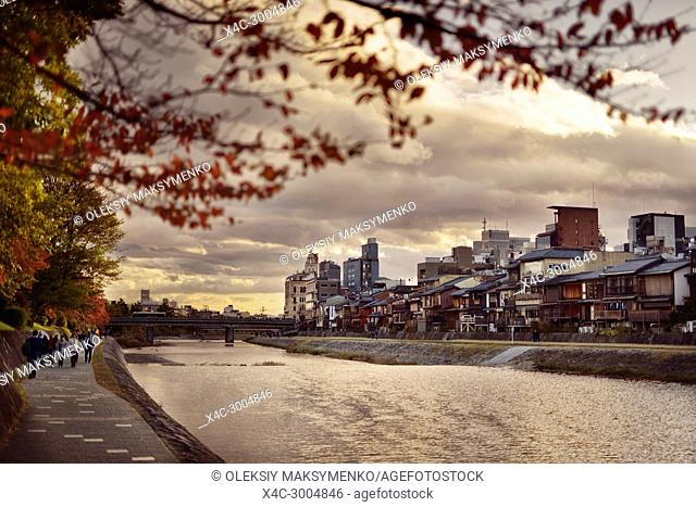 Pathways along Kamo River, Kamo-gawa, with Shijoo bridge in the background in a beautiful dramatic autumn sunset scenery in Kyoto, Japan