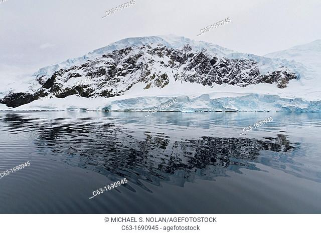 View of calm seas and reflected mountains surrounding Neko Harbor on the western side of the Antarctic Peninsula, Southern Ocean