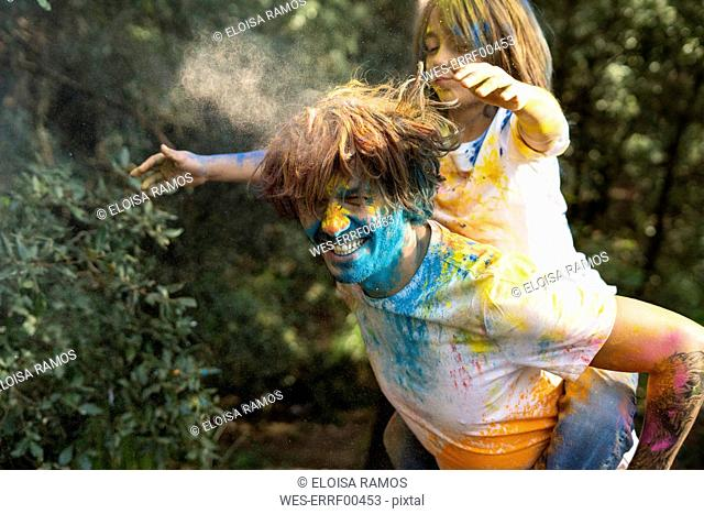 Father carrying son piggyback, full of colorful powder paint, celebrating Holi, Festival of Colors