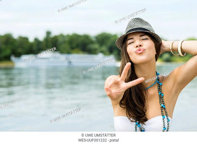 Portrait of smiling young woman showing victory sign on the beach