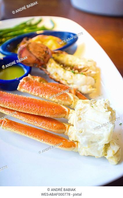 Seafood dish with crab legs, lobster tail and shrimps in butter sauce