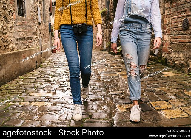 Low section of wo women walking in picturesque old town, Greve in Chianti, Tuscany, Italy