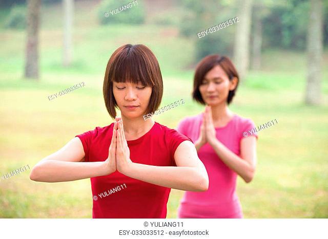 asian girls performing yoga outdoor