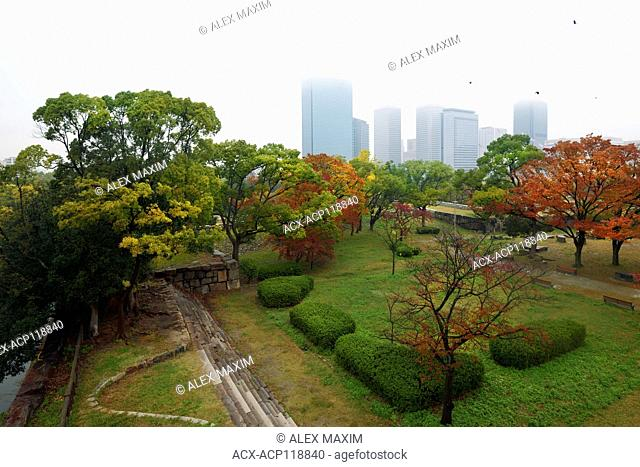 Osaka Castle Park colorful trees on a beautiful misty autumn morning with Osaka city skyline scenery of Chuo-ku financial distric high-rise towers in the...