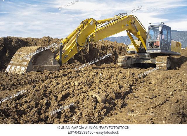 Earthmoving excavator preparing the construction site soil. Low angle shot