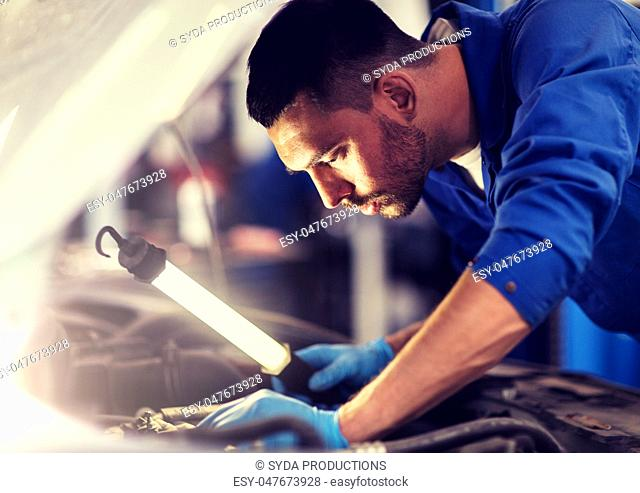 mechanic man with lamp repairing car at workshop