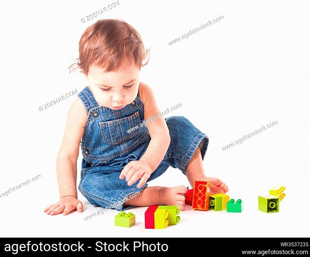Baby playing with color blocks isolated on white