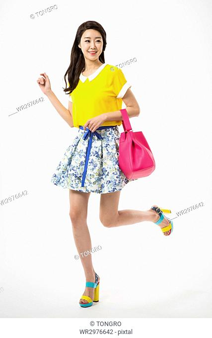 Young smiling woman in casual clothes walking holding bag