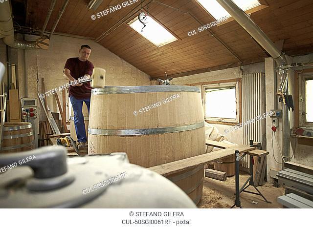 Worker hammering barrel in shop