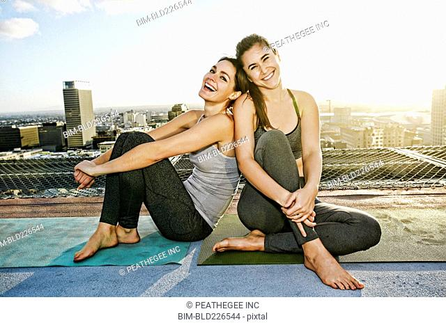 Caucasian woman relaxing urban rooftop after yoga