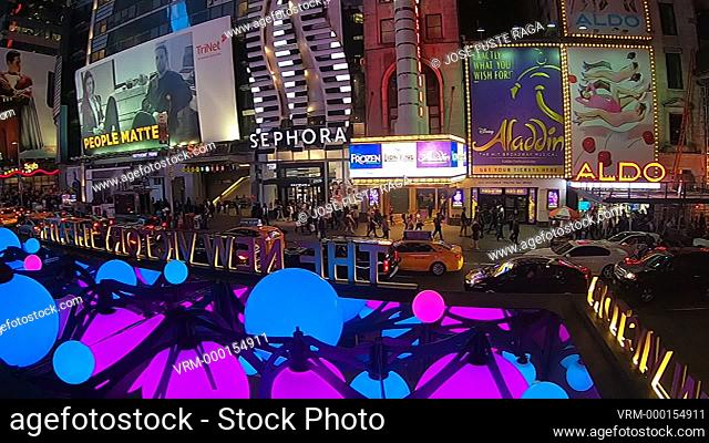 Bright neon signage flashes over crowds in Times Square