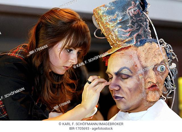Makeup artist in training working on an actor, fantasy latex mask, glued-on horror face with one eye, Berlin, Germany, Europe