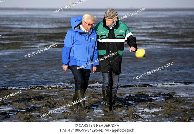 German federal president Frank-Walter Steinmeier can be seen with the head of the National Park Detlef Hansen (R), standing in the mud flats near Hamburger...