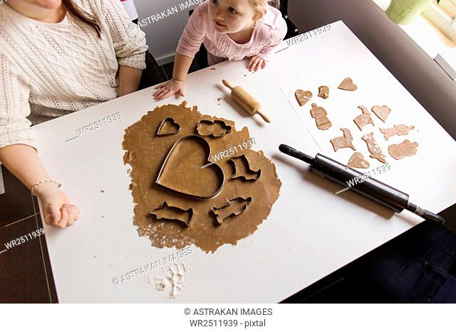 High angle view of mother and daughter preparing cookies at home
