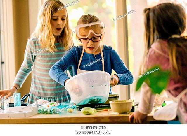 Girls doing science experiment, mixing green liquid in bowl