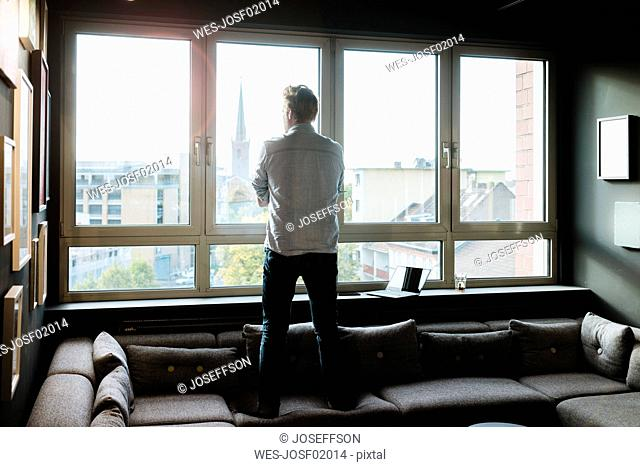 Businessman in lounge area of an office looking out of window