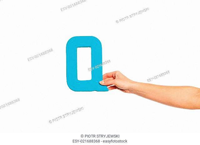 hand holding up the letter Q from the right