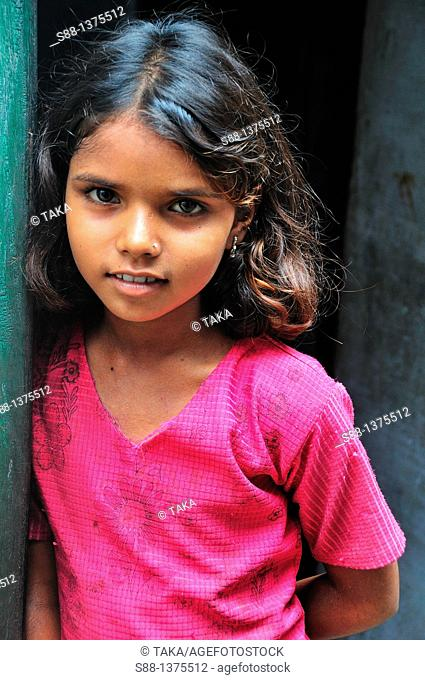 Young girl at narrow street of the old town near the Ganges River