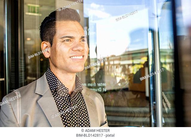 Hispanic businessman looking out window