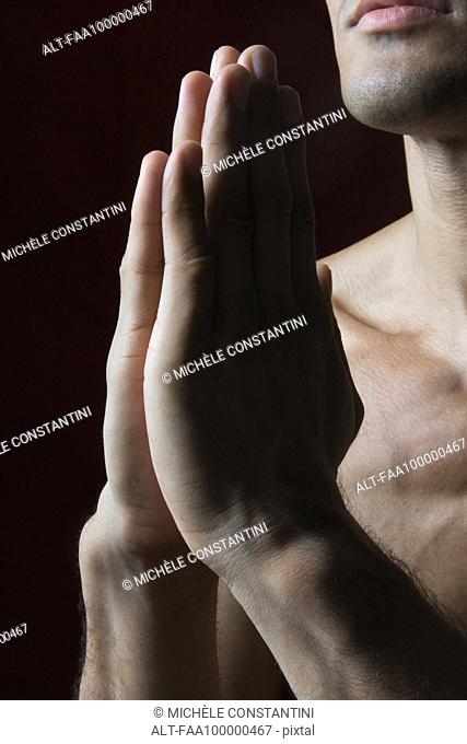 Barechested man with hands clasped in prayer, cropped