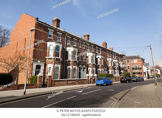 Three storey terrace houses with bay windows and front gardens