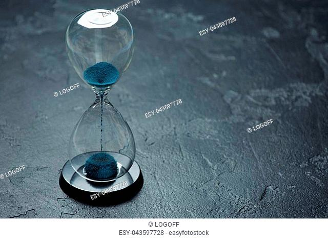 Image of hourglass with blue sand on black background, space for text