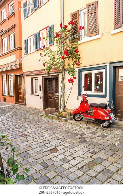 red vespa scooter in front of historic houses in the historic part of esslingen, baden-wuerttemberg, germany