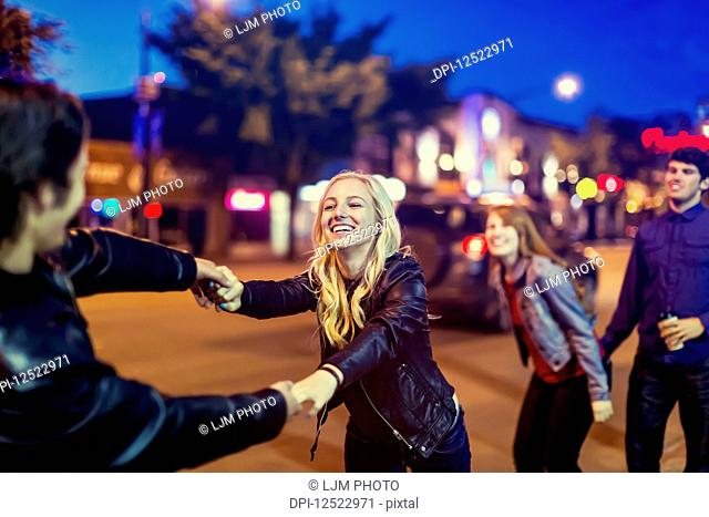Two young couples being playful on the sidewalk beside a city street at dusk; Edmonton, Alberta, Canada