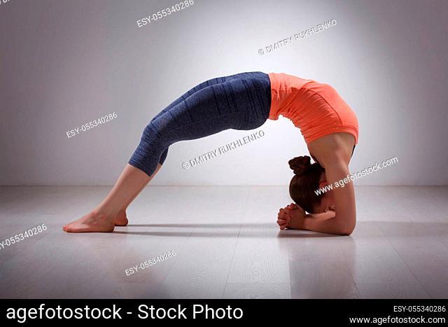 Beautiful sporty fit yogini woman practices yoga asana viparita dandasana - upward facing two feet staff pose in studio