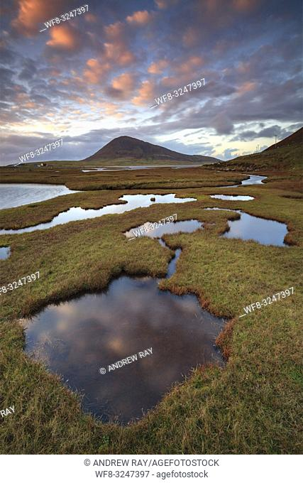 Sunset reflected in pools of water at Northton Salt Marsh on the Isle of Harris, with the 368m summit of Ceapabhal on the islands most westerly promontory in...
