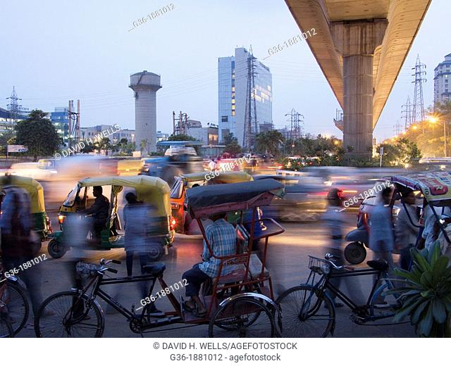 Commuters and bicycle rickshaw drivers swarm the Gurgaon Metro station south of Delhi, India