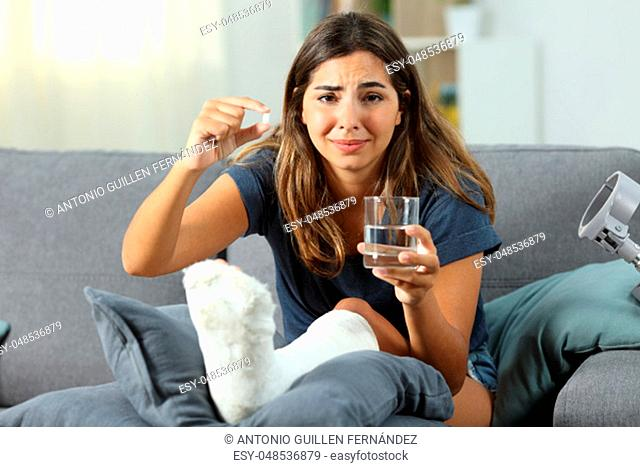 Sad disabled woman suffering and showing a pill sitting on a couch in the living room at home