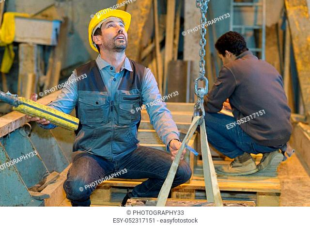 worker using an industrial hoist with the chain in factory