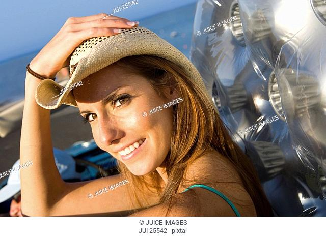 Smiling woman wearing straw cowboy hat