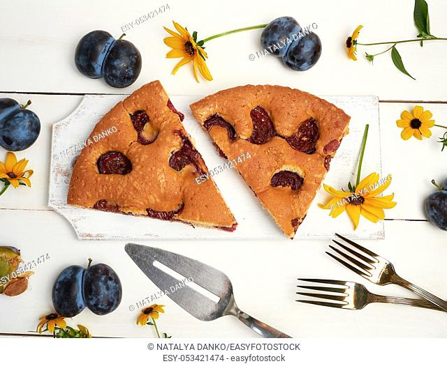 two slices of biscuit plum cake on a white wooden board and fresh fruits, top view
