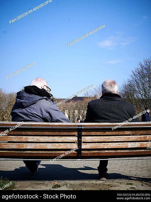 26 March 2020, Berlin: On the Carl-Zuckmayer-Bridge at Schöneberg town hall two elderly gentlemen are reading the newspaper on Thursday afternoon