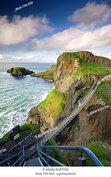 Young woman crossing Carrick-a-Rede rope bridge on the Causeway Coast, County Antrim, Ulster, Northern Ireland, United Kingdom, Europe