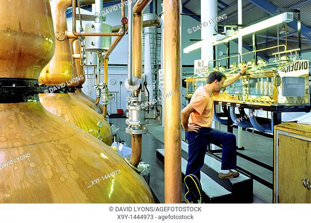 Laphroaig whisky distillery, Isle of Islay, Scotland  Still man checking levels in the spirit safe beside copper pot stills