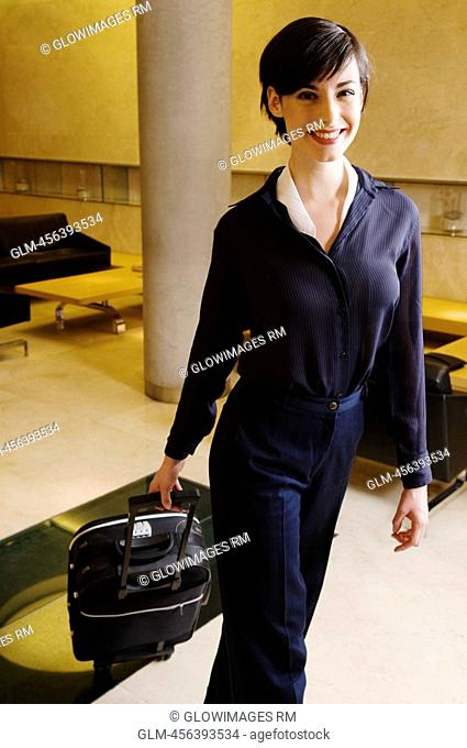Portrait of a businesswoman carrying luggage