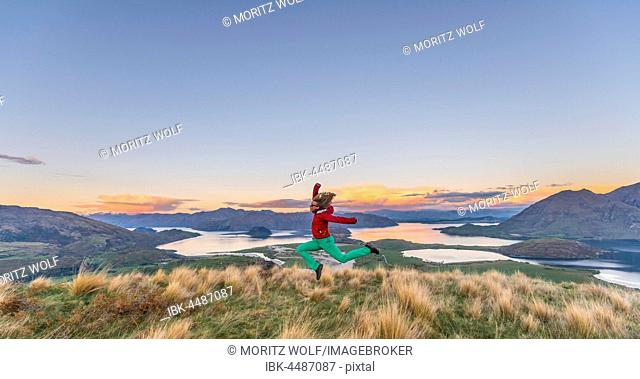 Hiker jumping in the air, view of Lake Wanaka and mountains, sunset, Rocky Peak, Glendhu Bay, Otago, Southland, New Zealand